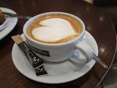 Flat white coffee with heart shape made of milk on top