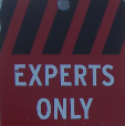 CLose up of ski warning sign, reading 'Experts Only'.