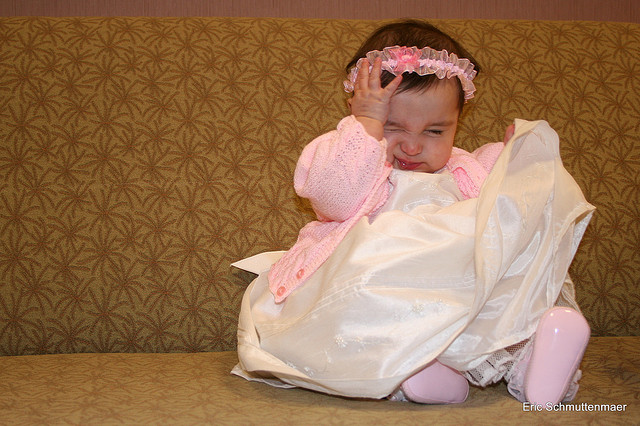 Young child wearing a white and pink wedding outfit and trying to remove her itchy headband