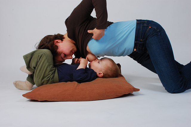 Mother kneeling over her breastfeeding toddler, by Mothering Touch