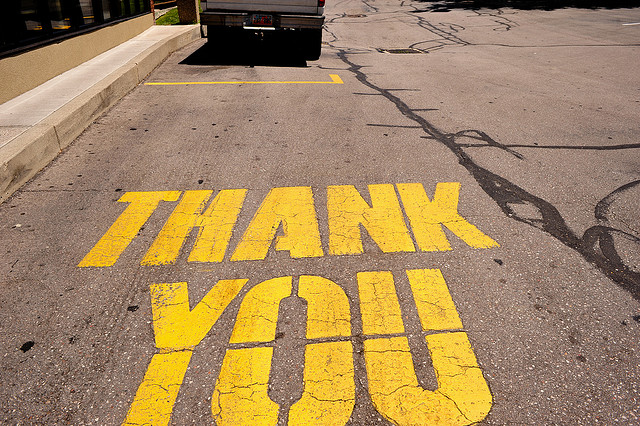 A thank you sign printed in yellow on the road